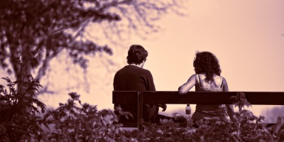Two people sitting on a park bench